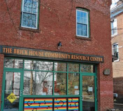exterior view of a multistory building with a door at ground level and signage identifying it as the Brick House Community Resource Center