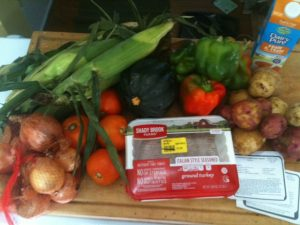 an array of fresh vegetables, a package of ground turkey, a quart of half-and-half, recipe cards
