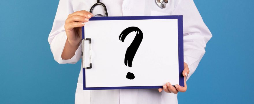 Doctor holding sign with question mark