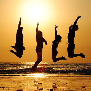 teens jumping on beach, silhouetted by setting sun behind them