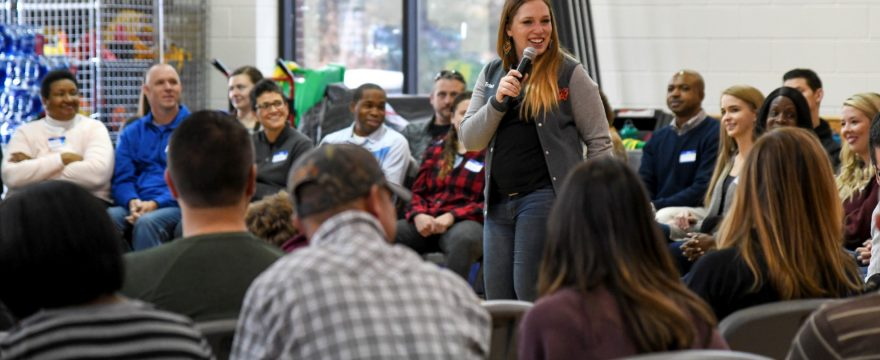 20-something, smiling, white woman holds microphone and speaks to engaged group of people