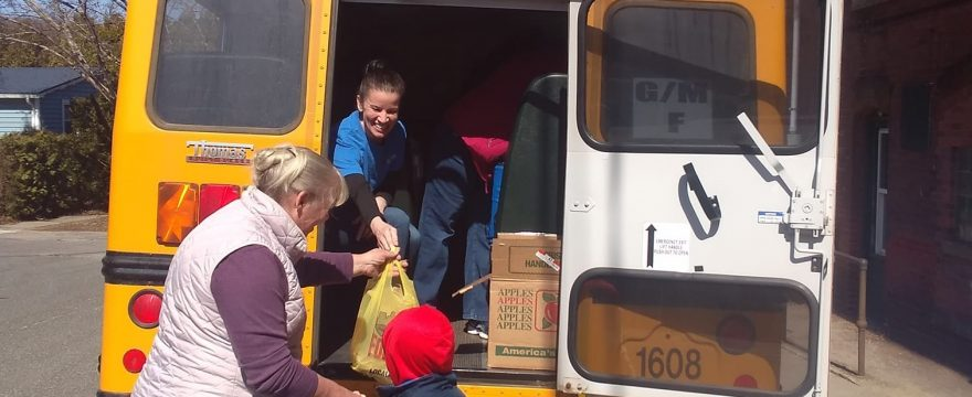 Smiling adult inside a yellow school bus hands a bagged to-go meal through the open rear door to an adult standing several feet away. The adult receiving the meal is holding hands with a child in a blue coat and red hat.