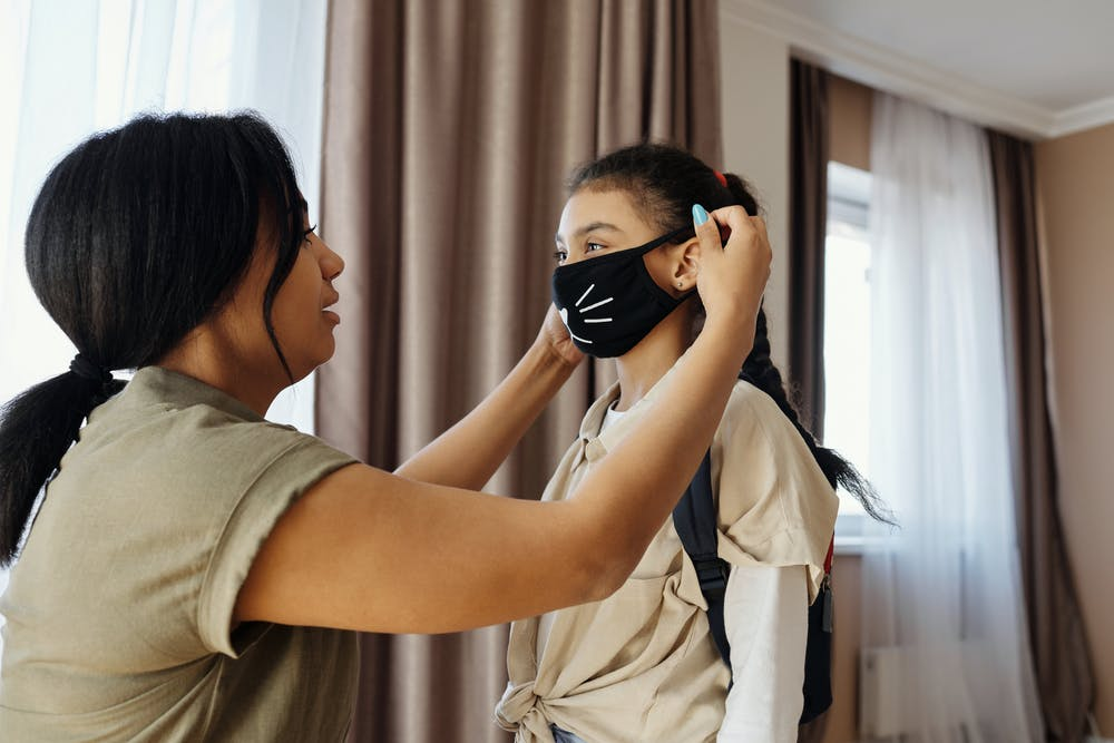 Mom fitting daughter with mask that has whiskers sewn onto it.