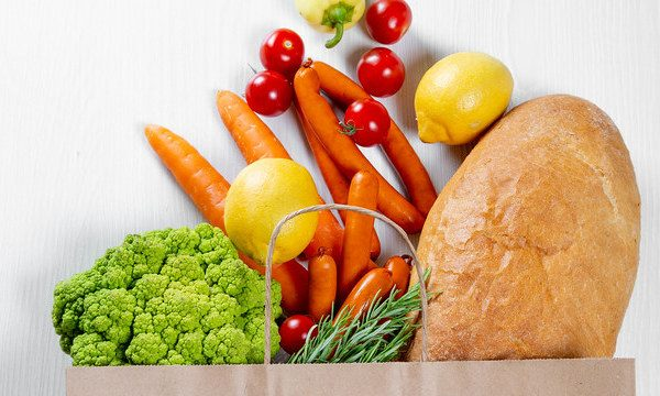 vegetables and bread in top of grocery bag