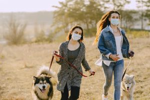 Teens or young women running outside with dogs on leashes, wearing medical style masks.