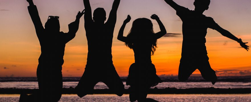young people or kids jumping in front of a sunset sky, so only their silhouettes are visible against the sky