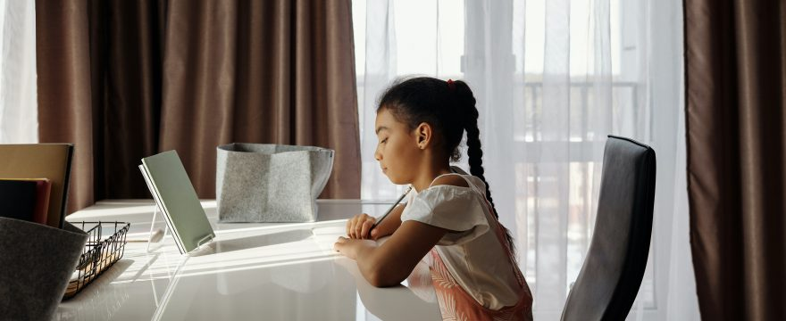 Photo of a girl sitting at a table learning remotely, reading. Side view, in front of a window with a sheer curtain. She looks serious but not sad.