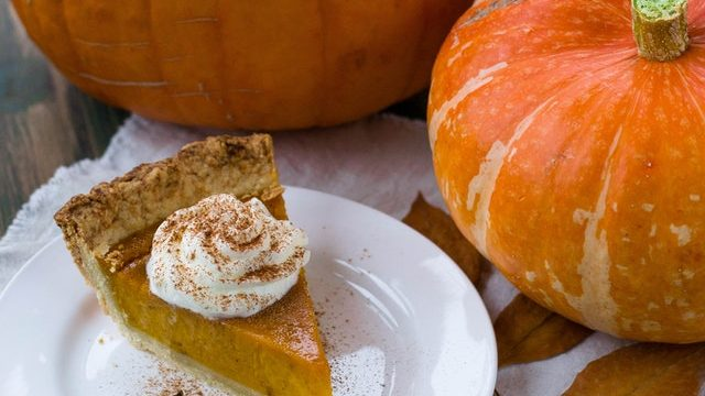 Photo of two pumpkins on a table next to a piece of pumpkin pie on a plate, looking festive.
