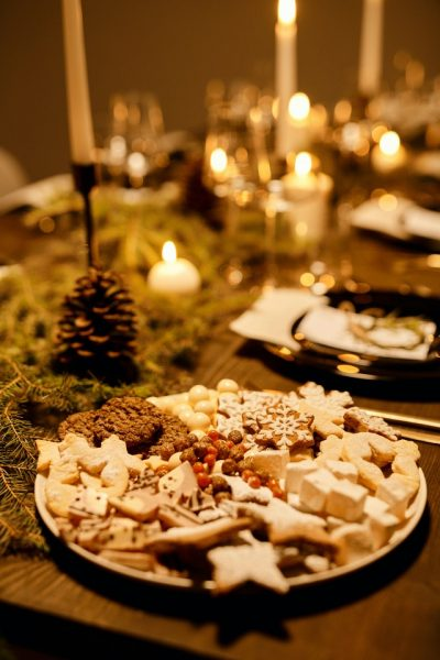 holiday cookies cut into snowflakes and other winter themed shapes on table with candles, looking festive