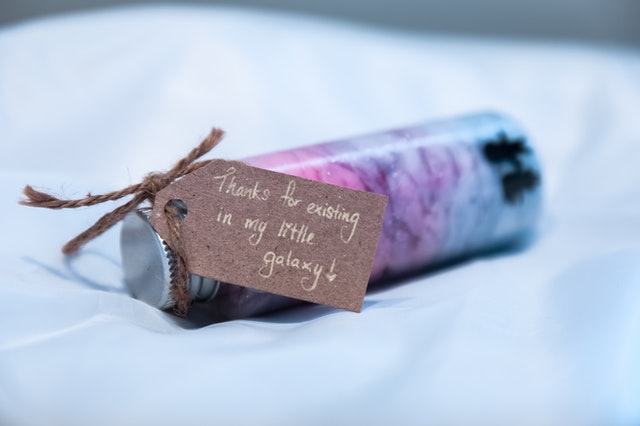 "A small bottle with colored soap or sand that has a tag attached, saying ""thanks for existing in my little galaxy."""