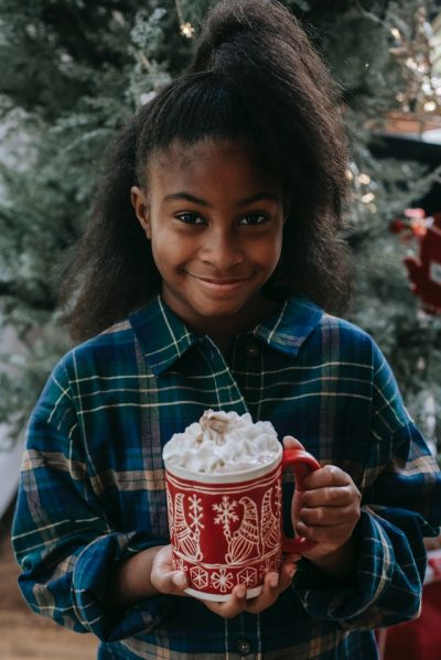 Girl smiling with cup of festive hot chocolate