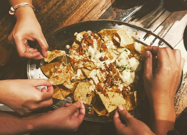 hands reaching for nachos on a plate