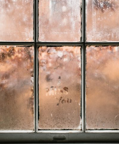 "A frosted window pane with the words ""I miss you "" written with someone's finger"