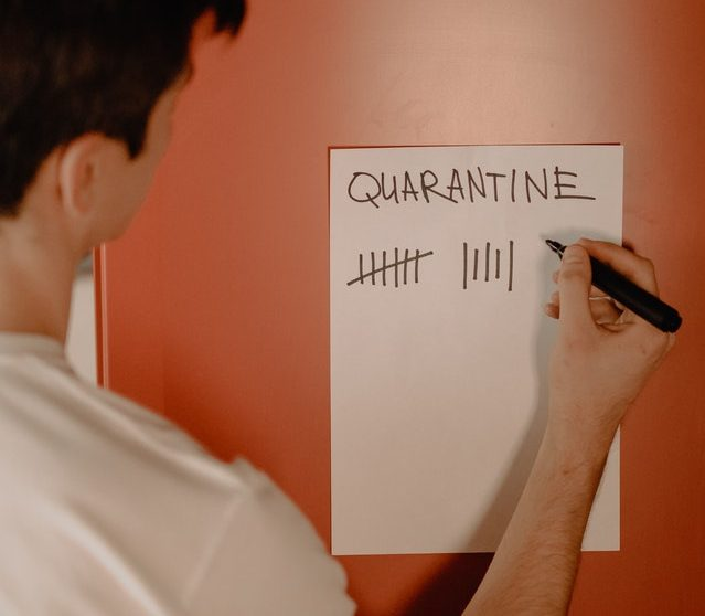 Image of a young man crossing off days of quarantine on a piece of paper