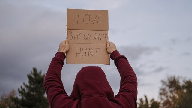 """A person wearing a sweatshirt with a hood facing away from the camera, holding a sign that says """"Love shouldn't hurt."""""""